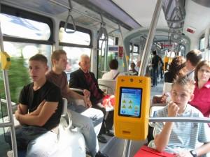 Салон трамвая. Желтая штука - информатор, контроллер билетов. Сзади видно красное табло с названием следующей остановки или рекламой. Остановки еще озвучиваются